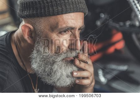 Thoughtful mature bearded biker is smoking while locating in garage. Portrait. copy space on right side