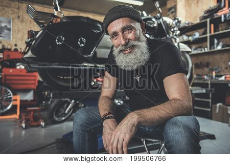 Happy bearded mature biker is sitting near motorbike. He glancing at camera with smile. Portrait