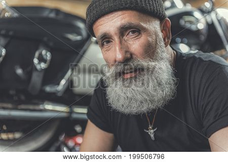 Joyous aged bearded biker is sitting afore motorbike and looking at camera with sincere interested smile. Portrait. Copy space on left side