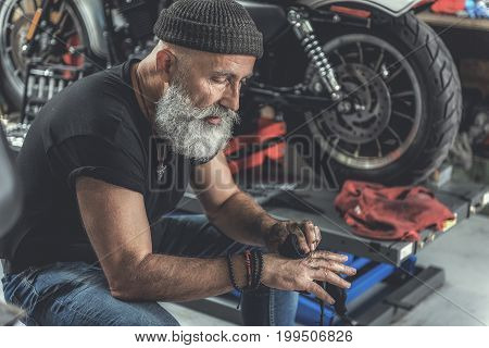 Serious mature bearded biker is sitting near motorcycle and making his hands clean through piece of cloth