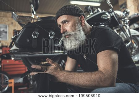Mindful old bearded biker is cleaning hands through small rag. He sitting near motorcycle and looking ahead with wistfulness. Low angle