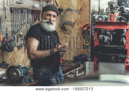 Glad elder biker is standing near work table and looking at camera with assurance. He cleaning hands through piece of cloth. Portrait