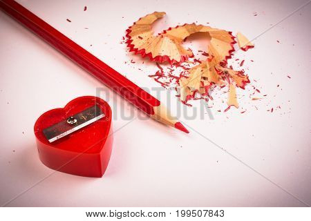 The red sharpener of heart shape with red sharpen wooden pencil are on white background.