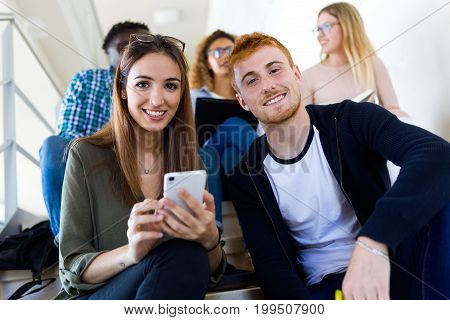 Two Students Using They Mobile Phone In A University.