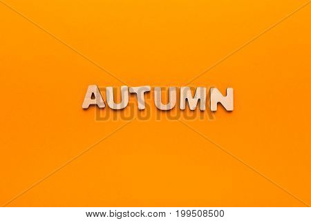 Word Autumn made of wooden letters on orange background. Month planning, timetable concept
