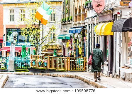 Quebec City Canada - May 30 2017: BiBi & Cie Chapelier store sign with man in coat walking by colorful buildings in old town on Rue Garneau