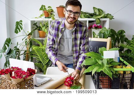 Male florist selling flowers at his shop