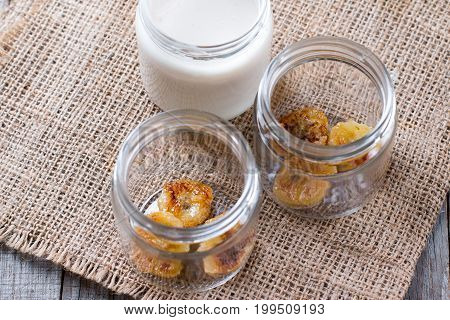 Bananas in glass jars on a wooden background