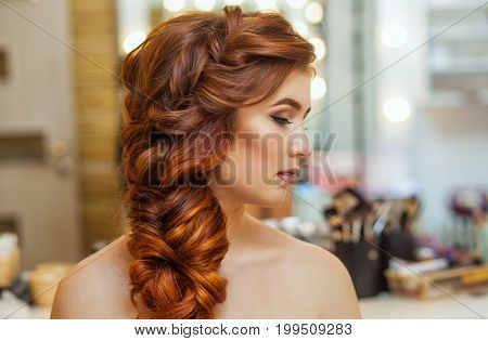 Beautiful with long red-haired hairy girl hairdresser weaves a French braid in a beauty salon. Professional hair care and creating hairstyles.