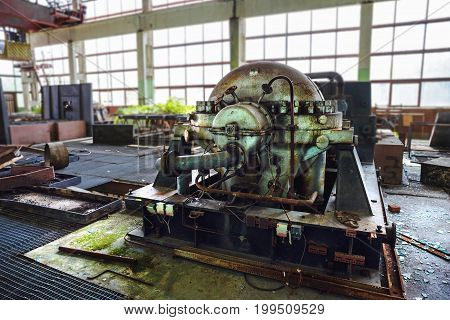 Iron rusty industrial equipment, machine in an abandoned factory in a large abandoned shop