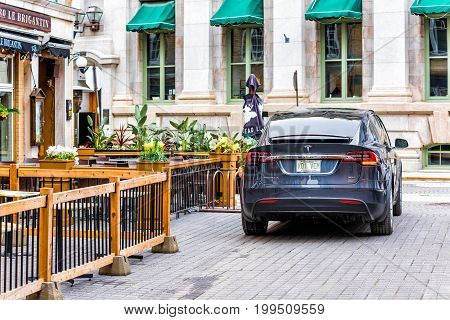 Quebec City Canada - May 30 2017: Blue Tesla Model X driving on cobblestone road in lower old town street called rue Sault-au-Matelot by restaurants stores and souvenir shops