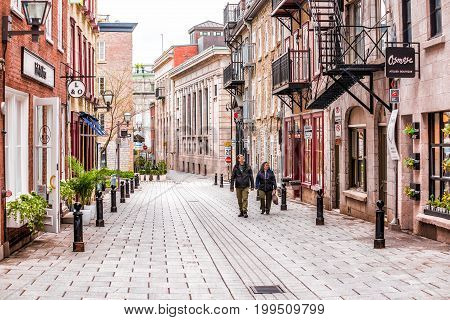 Quebec City Canada - May 30 2017: Lower old town street called Rue du Sault-au-Matelot with tourist couple walking on cobblestone