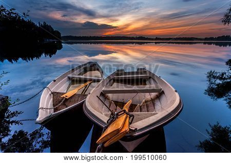 Summer evening with boats in the lake and sunset in Finland.