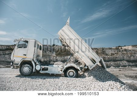 Truck unloads white limestone gravel to crushed stone quarry, toned