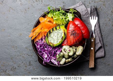 Budha bowl. Raw vegetables with beans, grilled avocado and bell pepper on slate background