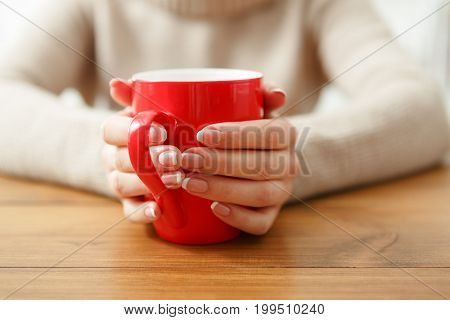 Female holding a cup of hot drink while sitting at wooden table, shallow depth of field.