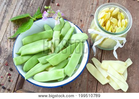 Fresh green and yellow wax beans on a wooden table