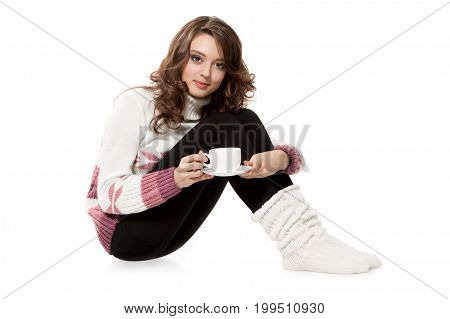 Young girl in a crocheted clothes with cup of coffee