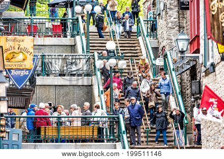 Quebec City Canada - May 30 2017: People walking down famous stairs or steps on lower old town street called Rue du Petit Champlain by restaurants