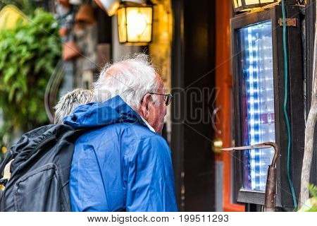Quebec City Canada - May 30 2017: Lower old town street called Rue du Petit Champlain with older couple looking at menu of restaurant closeup