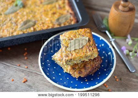 Pieces of vegetable cake with red lentils and bay leaf.