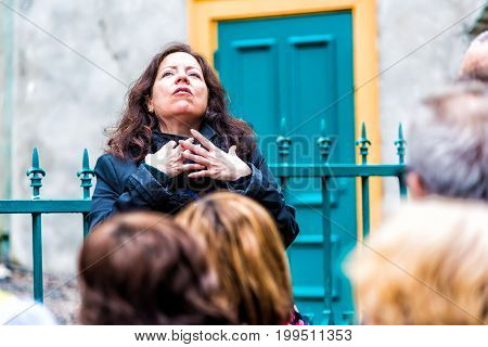 Quebec City Canada - May 30 2017: Closeup of tour guide emotionally gesturing and talking or explaining about old town history with group listening