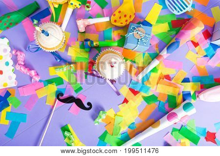 Celebration theme filled with party accessories on a purple background