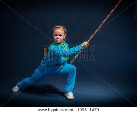 Girl in a blue wear engaged wushu against a dark background