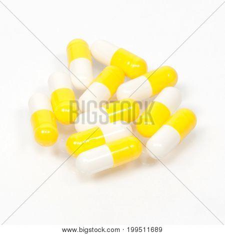 Yellow white capsule pills on white background