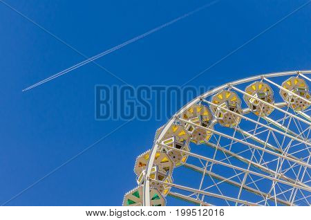 Ferris wheel with colored cabins against a clear blue sky at a funfair in Lyon against a clear blue sky at a funfair in Lyon while an plane is passing by