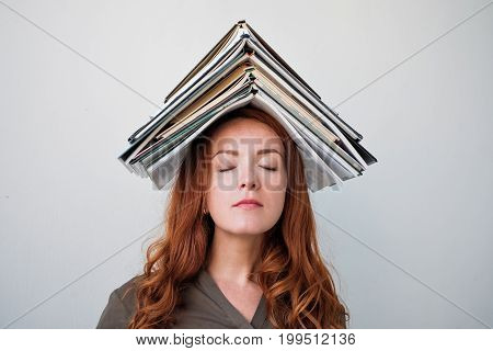Attractive young woman with red hair balancing a book on her head.