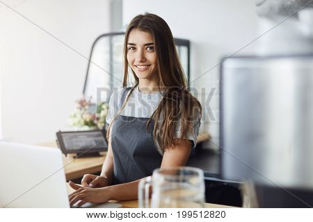 Young female entrepreneur running her first business in a newly opened cafeteria
