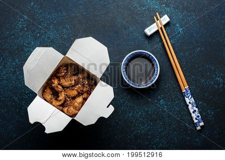 Chicken teriyaki in box and chopsticks on dark background with soy sauce. Top view.