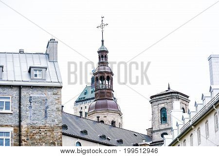 Quebec City Canada - May 29 2017: Church tower steeple of Notre Dame Cathedral closeup with cross and rooster