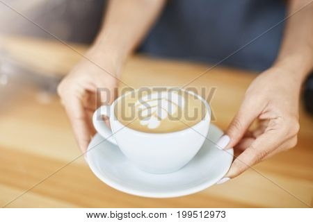 Close up of woman hands serving a cappuccino in a cup with latte art. Barista concept.