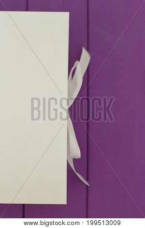 White box on the tie on a purple wooden background. Mocap