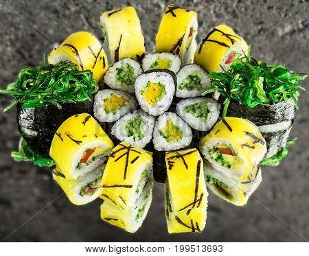 Vegetarian rolls and chuka gunkan over concrete background