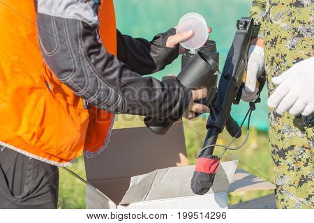Two persons loading paintball gun with balls outdoors