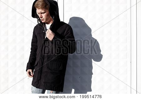 Young stylish redhead man in trendy outfit posing against urban background.