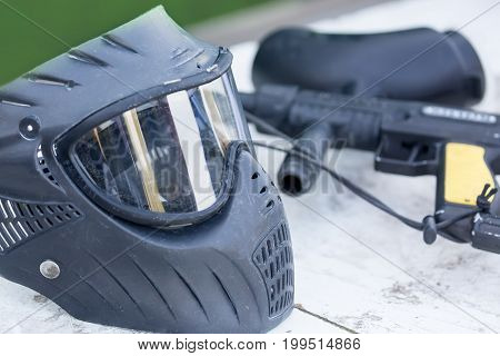 Paintball ammunition. Black helmet and gun outdoors. Close up image.