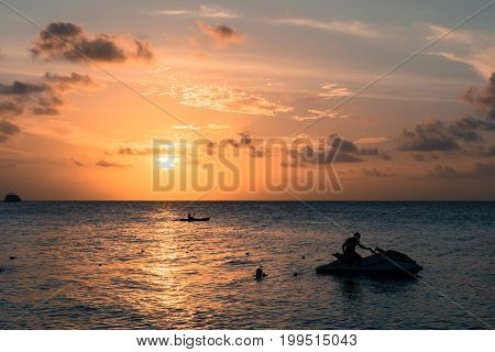 Horizontal picture from the beach of a man silhouette sitting on jet ski during sunset time with cloud sky at Maafushi in Maldives.