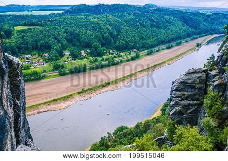 Elbe river with small village in front of Bastei sandstone rocks in Saxon Switzerland, Dresden, Germany.