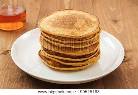 Vegan butternut squash puree pancakes on white plate with maple syrup. Healthy gluten free breakfast on wooden table