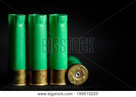 Three Standing And One Lying Under The Sleeve Of A Cartridge For The Shotgun Isolated On Black Backg