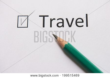 To travel. To make dream come true. The word TRAVEL is written on white paper in pencil marked with  tick
