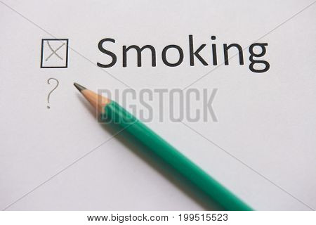 Quit smoking. The word SMOKING is written on white paper with cross and gray pencil.