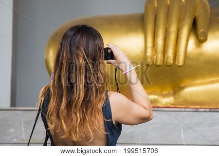 Woman taking pictures of golden buddha statue.