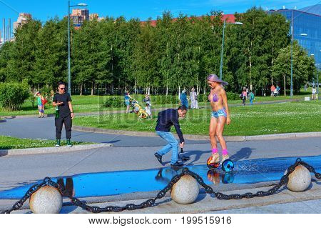 St. Petersburg Russia - August 1 2017: Park 300th anniversary of St. Petersburg videographer videotapes a girl who rides a gyroscooter.