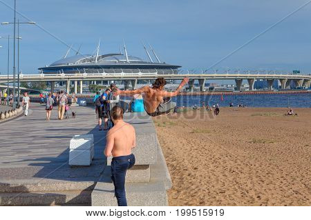 St. Petersburg Russia - August 1 2017: Park 300th anniversary of St. Petersburg young man practicing parkour in the city park.