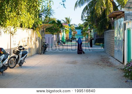 MAAFUSHI MALDIVES - MARCH 01 2016: Horizontal picture of muslim local woman sweeping the sand streets in Maafushi Maldives